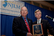 Joseph S. Roth accepts the Distinguished Public Service Award from Pres. Tim McDonough