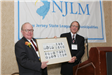 Outgoing NJLM President Stiles presented with a commemorative photo by NJLM Executive Director Bill