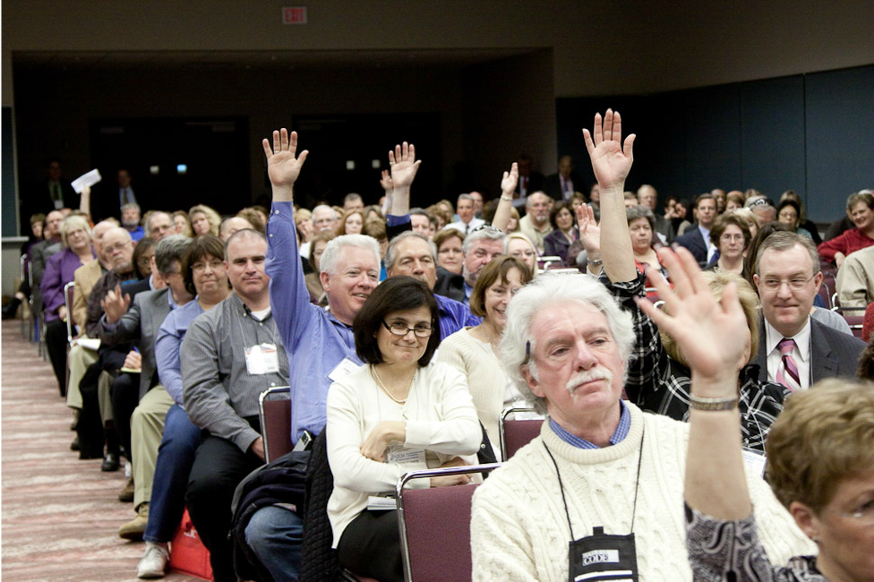 Session audience members raise hands to participate