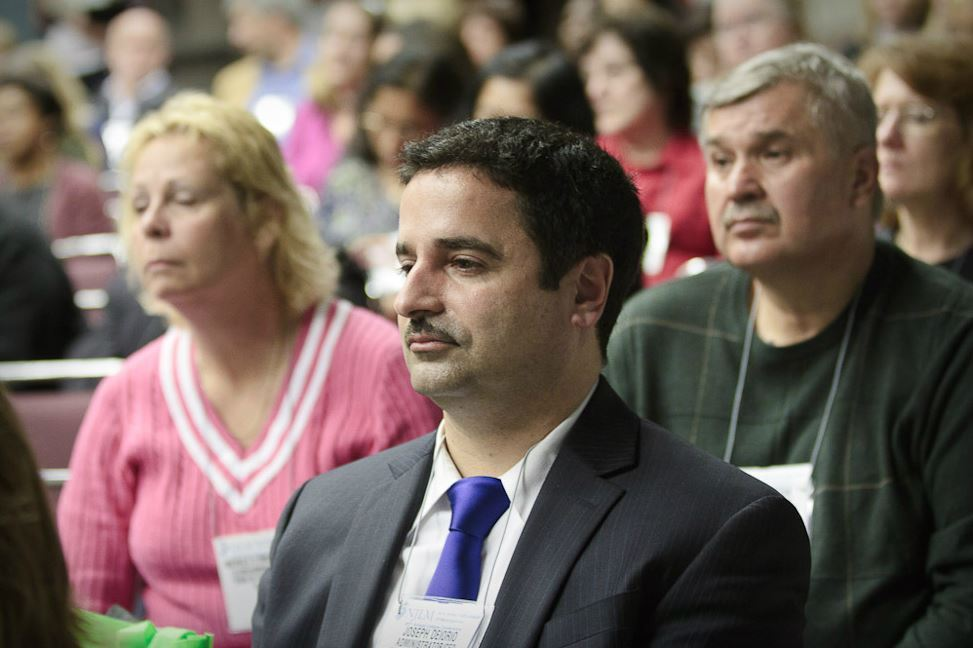 Man in the Audience Listens to Speaker