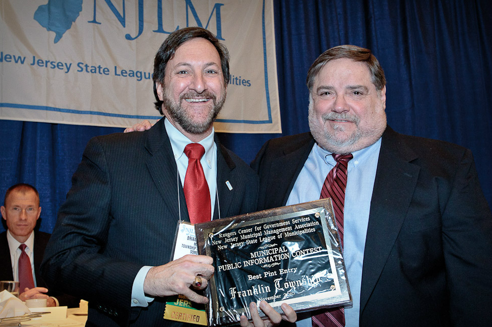 A Franklin Township representative (l) accepts the Municipal Public Information Contest prize from RU's Zalkind