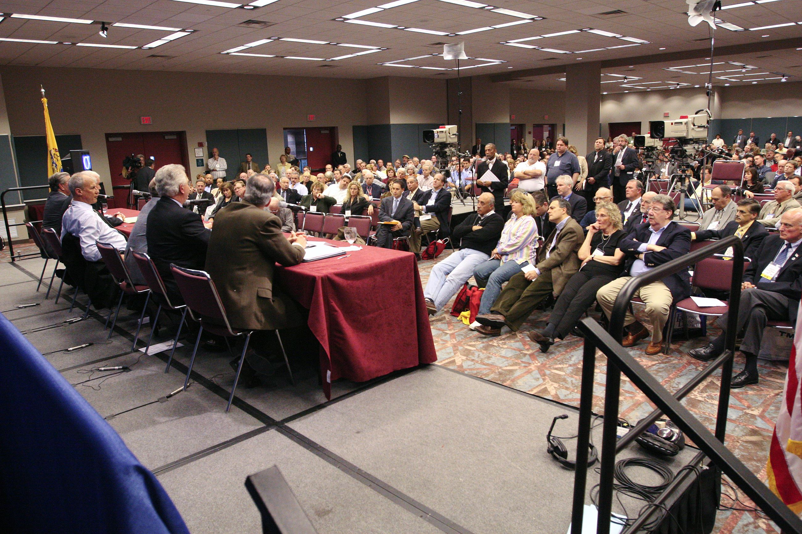 Audience members stand at microphone to ask legislative leaders panel questions